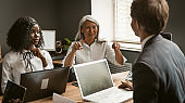 Multi ethnic team at business meeting in office. Focus on Asian white-headed mature businesswoman gesturing while presenting ideas to colleagues