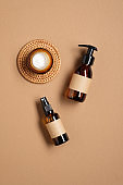 Amber glass pump bottle and sprayer with blank labels and jar of moisturizer cream on brown background. Flat lay, top view. Beauty product packaging design, branding.