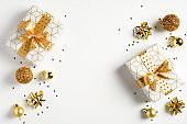 Happy New Year banner. Christmas design gold gifts box, golden balls, glitter confetti stars on white background. Decoration objects viewed from above.