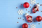 Blue Christmas background with red balls and gloves, white snowflakes, Xmas decorations. Vintage Christmas flat lay style composition, top view.