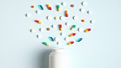 Colorful pills and capsules spilling from a white bottle top view. Creative layout with medical tablets, drug of painkillers, antibiotics, vitamins and jar. Pharmacy and medicine concept