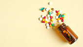 Colorful pills and capsules spilling from a bottle top view. Medical tablets, drug of painkillers, antibiotics, vitamins and glass jar. Pharmacy store, medical clinic, drugstore banner design template