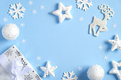 Christmas flat lay composition. Frame of white decorations, stars, reindeer, snowflakes, balls, gift box. Christmas, New Year, winter holidays concept.