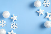 Christmas minimal style flat lay composition. Top view white snowflakes, stars, balls, Xmas decorations on blue background. Winter holidays, New Year, Christmas concept.