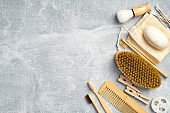 Set of bath accessories on stone background. Flat lay zero waste beauty products and organic cosmetic. Top view SPA brush, bamboo toothbrushes, loofah sponge, natural soap, hair comb