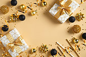 Christmas or New Year frame composition. Christmas decorations in gold and black colors and gift boxes on golden background with copy space for text. Flat lay, top view.