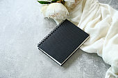 Wedding photo album mockup with beige cloth and peonies on concrete stone background. Flat lay, top view