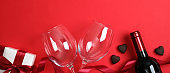 Valentines Day background with bottle of wine champagne, two glasses, white gift box with red ribbon bow heart shaped candies. Top view table setting for Valentines day. Romantic dinner couple concept