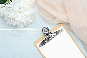 Flat lay blank paper clipboard, beige cloth and peony flowers on rustic blue wooden table. Top view with copy space. Wedding planner, checklist, to do list concept.