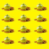 Green apple with measuring tape pattern on yellow