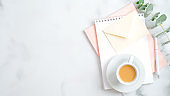 Feminine workspace with wedding to do list, envelope with love letter, pink notepad, cup of coffee, pen, eucalyptus leaf. Flat lay, top view. Wedding, bridal, marriage concept.