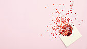 Envelope with red confetti on pink background. Top view with copy space. Valentines Day, Mothers Day, birthday greeting card template.
