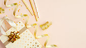 Shopping bag with presents, party streamers and gold confetti stars on beige table. Birthday, Christmas or anniversary celebration concept. Flat lay, top view.