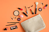 White makeup bag and cosmetic products spilling out on to pastel peach color background. Flat lay, top view. Stylish make up artist pouch with beauty products. Female make-up concept