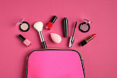 Make up bag with cosmetic products on pink background. Flat lay, top view. Beauty and fashion concept.