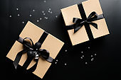 Luxury Christmas gift boxes with ribbon bow on black background with confetti. Xmas presents, New Years surprises. Flat lay, top view.