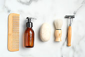 Set of eco-friendly wooden shaving accessories on marble background. Flat lay, top view.