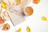 Flat lay autumn composition. Morning coffee cup, fallen leaves, women fashion glasses, beige scarf, diary on white table. Top view, overhead. Autumn breakfast at cozy home desk.