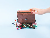 Lady hand bag upside down with make up items