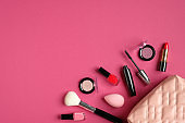 Make-up bag with decorative cosmetic products spilling out on to pink background. Flat lay, view from above. Elegant make up artist pouch with beauty products