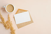 Kraft paper envelope with blank wedding invitation card mockup, cup of coffee and dry flowers on beige background. Flat lay, top view.
