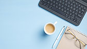 Blogger workspace with laptop keyboard, pink paper notebook, cup of coffee, pen on blue background. Minimal style home office desk table, flat lay, top view. Business and technology concept