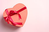 Heart shaped box with red ribbon bow on pink background, top view. Happy Valentines day greeting card template.