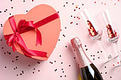 Flat lay composition with a heart-shaped box decorated with red ribbon, champagne bottle, glasses with confetti on pink background. Valentines Day celebration concept.