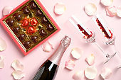 Romantic dinner. Box of chocolates, bottle of champagne and glasses with confetti on pink background decorated with rose petals. Valentines Day celebration concept.