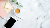 Flat lay home office desk. Women workspace with paper notebook, coffee cup, envelope, smartphone on marble table. Top view feminine background with copy space.