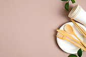 Bamboo cutlery set with biodegradable carton paper cups and plate on wooden table. Eco shop banner template with eco-friendly tableware and green leaves. Zero waste, plastic free concept.