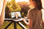 Teenage girl having video chat on laptop computer with her working mother