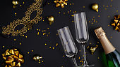 Champagne bottle with confetti stars, glasses, golden holiday decorations, masquerade mask on black background. Christmas party or New Year celebration concept. Flat lay, top view.