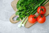 Wooden cutting board with fresh vegetables: tomatoes, parsley, green onion. Healthy organic food, salad ingredients top view