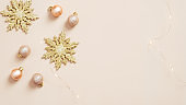 Christmas holiday decorations and garland on pastel beige background. Flat lay, top view.