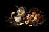 Dark vintage rustic kitchen - eggs, milk, flour, butter on black