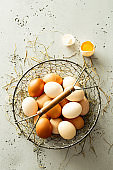Country eggs in a vintage metal mesh basket on grey stone background
