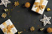 Black Christmas background with luxury gift boxes, golden glitter decorations, stars, confetti. Christmas, winter, new year concept. Flat lay, top view, overhead