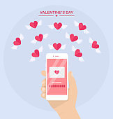 Valentine's day illustration. Send or receive love sms, letter, email with mobile phone. Human hand hold cellphone isolated on  background. Envelope, flying red heart with wings