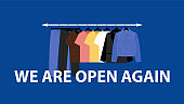 WE ARE OPEN AGAIN and clothes rack. Business after lockdown.