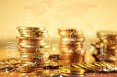 Double exposure of city and rows of gold coins for finance and banking.business investment and currency exchange concept.