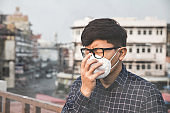 Can't breathe. Man wearing the respiratory protection mask against air pollution and dust particles exceed the safety limits. Healthcare, environmental, ecology concept. Allergy, headache.