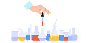 A hand is holding a dropper. Chemical Science Equipment glassware. Glass empty beakers,flasks,test tubes, bottles.