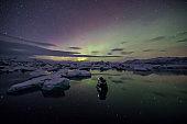 Aurora Borealis (Northern Lights) above Jokulsarlon Glacier Lagoon with photographer