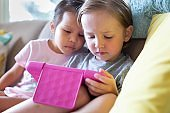Kids watching tv on tablet at home. Online education.