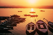 Orange Sunrise and people silhouettes in boats on Gang river, Varanasi