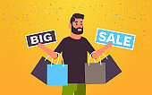 man holding purchases and big sale banners male customer with shopping bags special offer holiday discount concept flat portrait horizontal