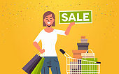woman holding sale banner female customer with trolley cart full of gift boxes special offer shopping concept flat portrait horizontal