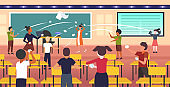 pupils demonstrating bad behavior throwing papers mocking and teasing female teacher during lesson bullying public disapproval concept school classroom interior horizontal