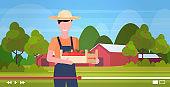farmer blogger holding wooden box with apples man vlogger in uniform blogging concept field farmland countryside landscape portrait horizontal